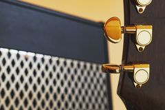 Guitar head with golden tuners in front of powerful vintage guitar amplifier with shiny metal grill stock photos
