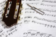Guitar head and tuning fork closeup on notes. Background Stock Photography