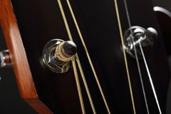 Guitar head with tuning pegs close-up. Wooden guitar head with strings and tuning pegs close-up Stock Photos