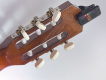 Guitar headstock backside, with installed clip-on tuner, that sh. The guitar headstock backside, with installed clip-on tuner, that shows the note e Stock Image