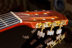 Guitar headstock on black reflecting surface Royalty Free Stock Image