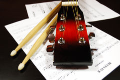 Guitar headstock and drum sticks. Blues time. Guitar headstock and drum sticks closeup against a blues sheet music Stock Photos