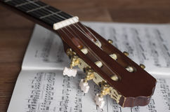 Guitar headstock with notes on wooden background. Close up, focus on headstock Royalty Free Stock Image