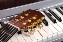 Guitar headstock on the piano keyboard Royalty Free Stock Photos