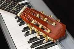 Guitar headstock on the piano keyboard Royalty Free Stock Photography
