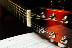 Guitar headstock and tuning pegs. Closeup against a blues sheet music in the darkness Stock Image