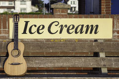 Guitar and Ice Cream - my kind of vacation!. Parlour-sized classical acousic guitar resting on a bench infront of an ice cream sign. Symbolic of vacation Stock Images