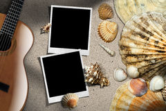 Guitar - Instant Photos - Seashells on Beach. Acoustic guitar, two blank instant photo frames on a sandy beach with a group of seashells - Beach vacation Stock Photography