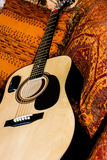 Guitar laying on a southwest designed afghan throw. A beautiful beige guitar, ready to play delightful and thrilling music if the right person picks it up. The royalty free stock images