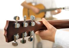 Guitar lesson. Or two musicians playing together, shot from behind one guitar, with shallow focus stock photo