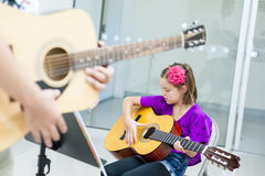 Guitar Lesson. Young girl being taught a guitar lesson in a classroom Stock Images