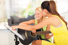 Guitar lesson. Young preteen girl having guitar lesson at home stock photo