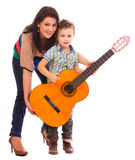 Guitar lessons. Mother teaching her kid to play guitar stock photo