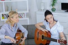 Guitar lessons girl playing guitar. Guitar lessons girl playing the guitar Stock Photo