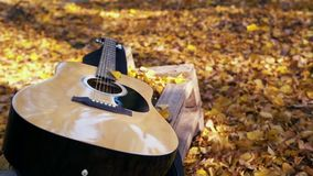 The guitar lies in the forest on the yellow leaves. Yellow leaves fall on the guitar. Autumn forest