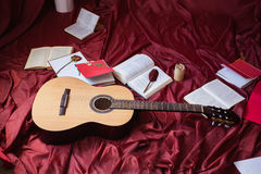 Guitar lying on red fabric, dried flowers, books on a red background. Scattered books, fountain pen, art atmosphere Royalty Free Stock Photo
