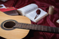 Guitar lying on red fabric, dried flowers, books on a red background Stock Photo