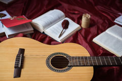 Guitar lying on red fabric, dried flowers, books on a red background. Scattered books, fountain pen, art atmosphere Royalty Free Stock Images