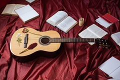 Guitar lying on red fabric, dried flowers, books on a red background Royalty Free Stock Photo
