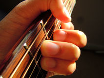Guitar chord. A hand close-up, playing a guitar chord on an acoustic guitar Stock Photography
