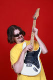 Guitar man. Rock guitarist playing the guitar over a red background Royalty Free Stock Photos