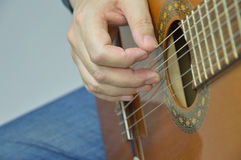 Hands and guitar - a man plays an instrument in a. The man playing the guitar in the frame arms, and musical instrument Royalty Free Stock Photography