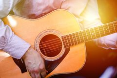 Guitar with a man`s male hands playing the guitar on wooden wall background, electric or acoustic guitar with nature light. Concep. T of guys boys band royalty free stock photo