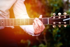 Guitar with a man`s male hands playing the guitar on wooden wall background, electric or acoustic guitar with nature light. Concep. T of guys boys band stock photos