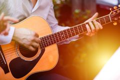Guitar with a man`s male hands playing the guitar on wooden wall background, electric or acoustic guitar with nature light. Concep. T of guys boys band stock photo