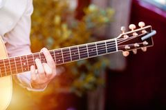 Guitar with a man`s male hands playing the guitar on wooden wall background, electric or acoustic guitar with nature light. Concep stock image