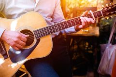 Guitar with a man`s male hands playing the guitar on wooden wall background, electric or acoustic guitar with nature light. Concep. T of guys boys band royalty free stock images