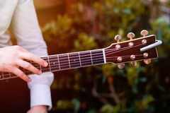 Guitar with a man`s male hands playing the guitar on wooden wall background, electric or acoustic guitar with nature light. Concep. T of guys boys band stock photography