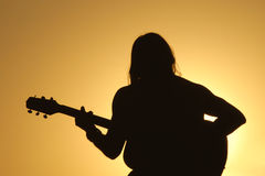 Guitar Man: Sunset Silhouette. A man sits silhouetted against a bright setting sun playing his guitar Stock Photography
