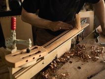 The guitar master makes guitar neck. The guitar master makes a guitar neck royalty free stock photography
