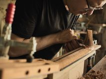 The guitar master makes guitar neck. The guitar master makes a guitar neck stock image