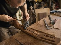 The guitar master makes guitar neck. The guitar master makes a guitar neck royalty free stock image