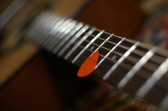 Guitar with a mediator. Six-stringed wooden guitar with a mediator Royalty Free Stock Photography