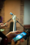 Guitar and mobile phone during live concert on stage Royalty Free Stock Images