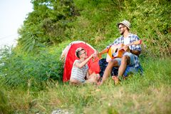 Guitar music in camp, good times. Guitar music and camping, two hipsters are having a good time royalty free stock photography