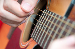 Guitar music. Singer hands on the acoustics guitar playing a folk song Royalty Free Stock Image