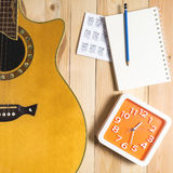Guitar with Music song writing equipment. On wooden floor Stock Image