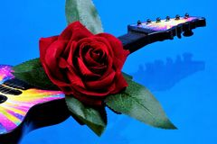 The guitar is a musical instrument and a red rose the Queen of flowers. Rose is a symbol of love, passion, decoration of holiday. Ceremonies. Guitar for royalty free stock images
