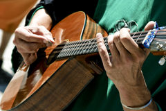 Guitar musician. A musician playing a guitar out in the sun Stock Photography