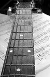 Guitar Neck. Acoustic guitar neck laying on sheet music stock photography