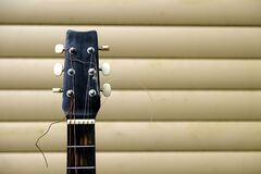 Free Guitar Neck And Head In Bad Condition With Broken Strings In Front Of House Wall Front View Closeup Royalty Free Stock Image - 189129126