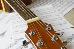 Guitar neck on the background of sheets with notes royalty free stock image