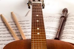 Guitar neck, drumsticks, recorder instrument and musical sheets. Guitar neck on background with drumsticks, recorder instrument and musical sheets Royalty Free Stock Photos