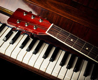 Guitar neck on old piano keys Stock Photos