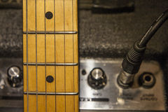 Guitar neck over amplifier device and audio cord Stock Image