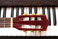 Guitar neck on piano keys Stock Photos